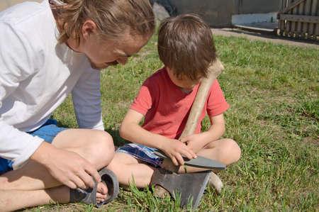 gad: Daddy teaching boy in ax blade sharpening