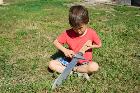 Boy learning in machete edge blade sharpening