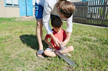 gad: Father teaching boy in machete blade sharpening