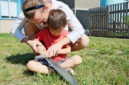 gad: Dad teaching boy in machete blade sharpening Stock Photo