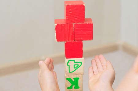 red cross: cruz roja de cubos de juguete en manos de los cabritos edificada de ni�o