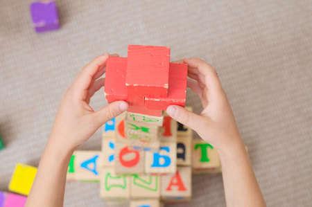 red cross: manos de un ni�o jugando edificio pir�mide de cubos con una cruz roja en la parte superior Foto de archivo