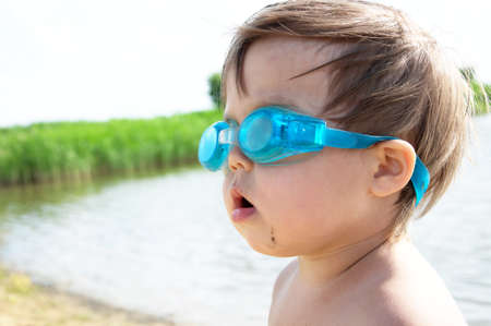 scuba goggles: Little cute girl summer portrait with goggles on the lake