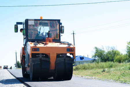 vibrator: HALBSTADT, RUSSIAN FEDERATION - AUGUST 8, 2016: road-roller paving new asphalt in the countryside