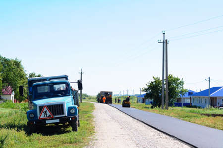 constructing: HALBSTADT, RUSSIAN FEDERATION - AUGUST 8, 2016: Constructing new asphalt in the village with transport Editorial
