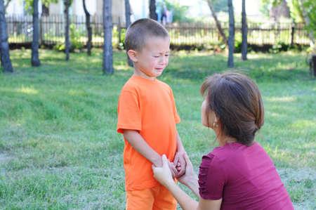 Madre calmar niño pequeño al aire libre