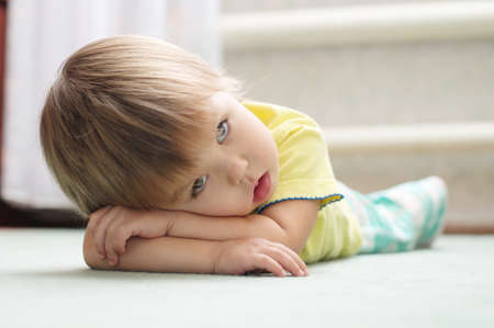 Little girl lying on the floor on arms Stock Photo
