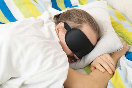 sleep mask: bearded young man sleeping with sleep mask in bed
