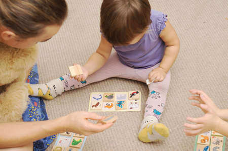 guess: Daddy and kids playing childrens lotto with figures of animals Stock Photo