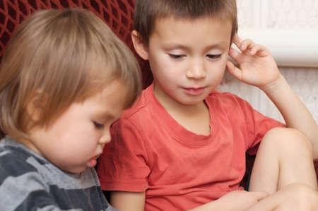 二人の小さな子供の兄弟一緒に本を探しています。 写真素材