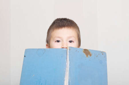 'hide out': Boy peep out from book, vintage and old book Stock Photo