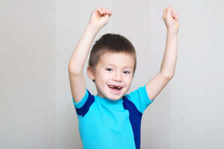 toothless: smiling happy boy greeting with hands up, toothless child Stock Photo