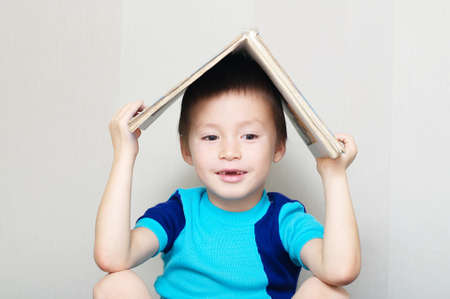 Happy boy with book on head making roof