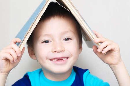 지붕을 만드는 머리에 책을 떨어 뜨린 우유 치아와 웃는 소년 스톡 콘텐츠