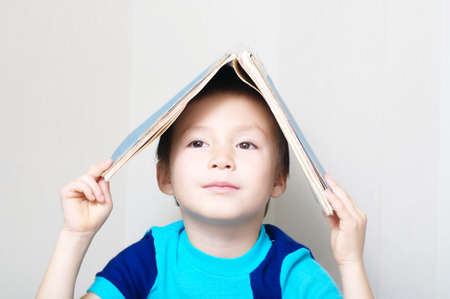 Smiling boy looking forward making book like roof