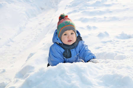 warm clothes: Winter activities concept - little girl outdoor playing in snow in warm clothes outside