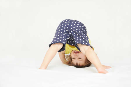 Happy little girl standing on head upside down isolated on white background Stock Photo