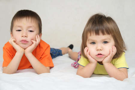 little boy and girl, brother and sister quarreling on bed, family relationships concept