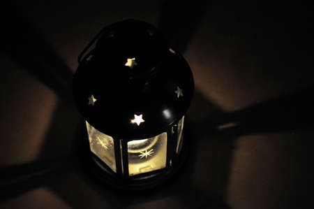 Candle lantern in dark with shades, shining star in black background with soft fire