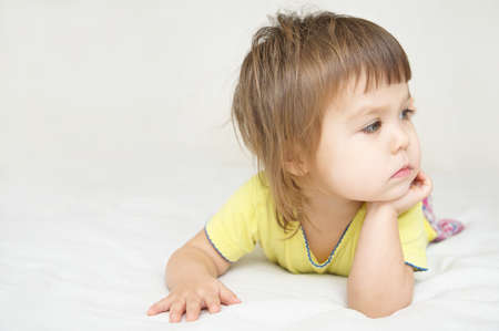 thoughtful child, thinking little girl lying on bed looking away, thinking about future concept Stock Photo