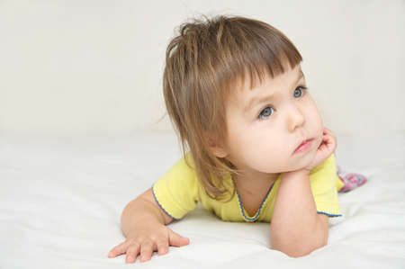 despondent: thoughtful child portrait, thinking little girl lying on bed looking away isolated, meditative person