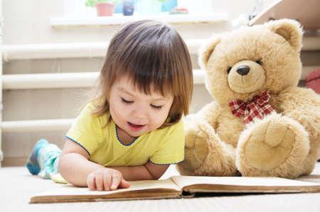 귀여운 소녀, 아이들의 교육 및 개발, 행복한 유년기, 웃는 곰, 장난감 함께 카펫에 그녀의 방에 누워 책을 읽고 아가씨