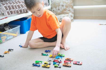 카펫에 재생하는 소년. 카펫에 집을 재생합니다. 어린이를위한 운송, 비행기, 비행기 및 헬리콥터 장난감, 미니어처 모델 스톡 콘텐츠
