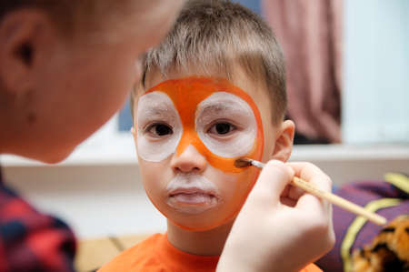 niños actuando: Make up artist making tiger mask for child.Children face painting. Boy  painted as tiger or ferocious lion. Preparing for theatrical performance. Boy actor playing role. Tiger mask face