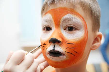 Make-up artist making tijger masker voor child.Children schminken. Boy geschilderd als tijger of woeste leeuw. Voorbereiding voor theatervoorstelling. Jongen acteur die rol. Tiger maskergezicht