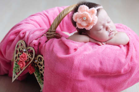 decoratiion: Newborn sleeping with knitted flower on head. Infant baby girl closeup lying on pink blanket in basket decorated with wooden hearts. Cute portrait of new child.