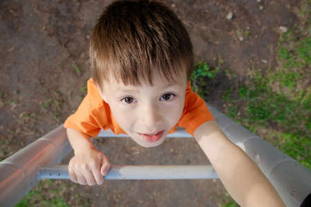 subdue: boy climbing stairs and playing outdoors on playground, children activity. Child portrait from above. Active healthy childhood concept