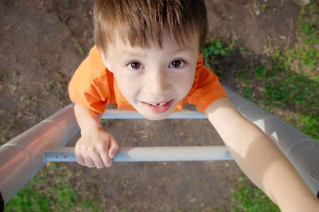boy climbing stairs and playing outdoors on playground, children activity. Child portrait from above. Active healthy childhood concept