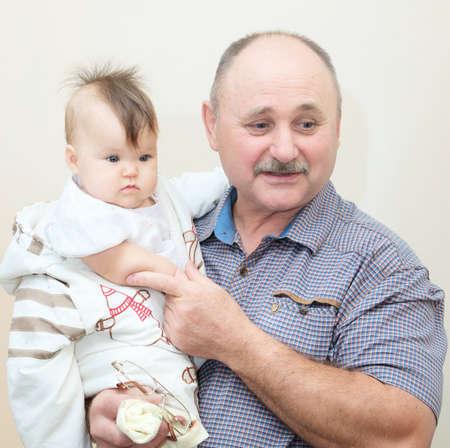 祖父と孫娘。年上の先輩と彼の小さな赤ちゃん孫一緒にポートレート。次世代の家族の
