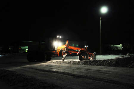 snow removal tractor cleaning snow, truck silhouette working at night cleaning road, city  infrastructure in winter, night work