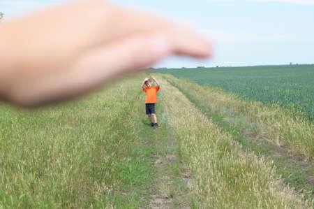 Big hand shelter little tiny boy in the field Reklamní fotografie