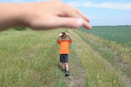 Big hand shelter little tiny boy in the field Stock Photo