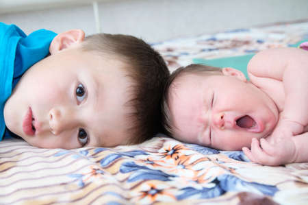 Brother and little newborn sister yawning lying on bed at home together Stock Photo