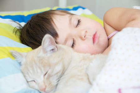 Little girl sleep with cat, favorite pet lying on child chest, Interactions between children and Cats