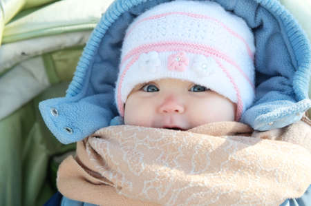 Happy smiling baby portrait in warm clothes in coat. Winter weather overall for little child