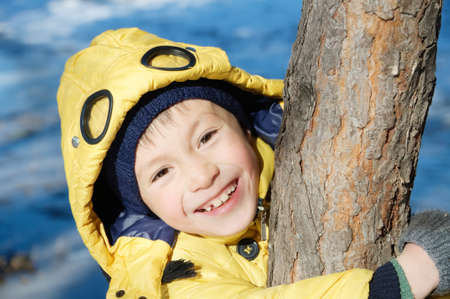 Boy portrait in coat looking from tree. happy smiling kid. schoolboy child 7 years Stock Photo
