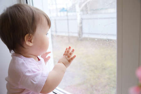 child looking out the window longing for some sunshine. curiosity childness. curious baby girl in pink clothes one year old on the window, inquisitive child at home at rainy day