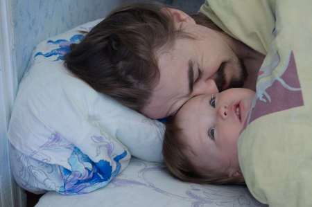 Little baby girl wake up in the morning. Parent tired sleeping. Father lying on bed. Happy family.
