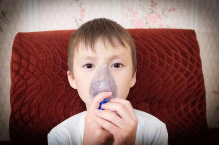 sick boy in nebulizer mask making inhalation, respiratory procedure by pneumonia or cough for child,  inhaler, compressor nebulizer,  nebules machine for health care. Kid catch cold Stock Photo