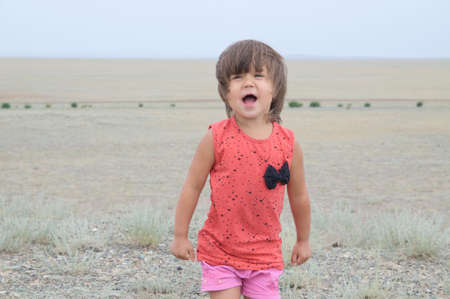 Little girl screaming in big landscape environment. Child emotionally saying loudly something, singing a song with expression