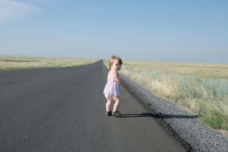 Running away little baby girl in steppe. Big landscape environment. Lonelyness concept. Travel in Middle Asia Kazakhstan