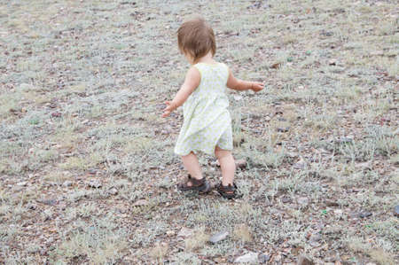 Child dancing outdoors. Little baby girl walking away. Running away little baby girl in steppe. Big landscape environment. Lonelyness concept. Travel in Middle Asia Kazakhstan Stock Photo