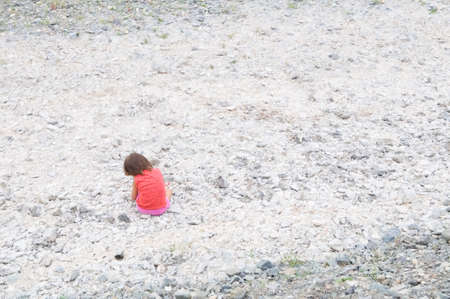 Child sitting in dried river bed in Middle Asia Kazakhstan among the white stones