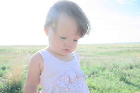 Little baby girl in steppe. Big landscape environment. Lonelyness concept. Travel in Middle Asia Kazakhstan