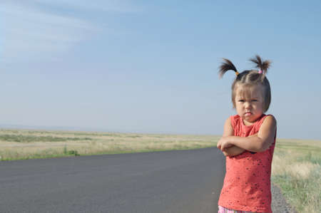 resentful child is standing and dont want to go anywhere defend own position . Little girl in kazakh steppe, cute adorable kid. Relationships with kids concept Stock Photo