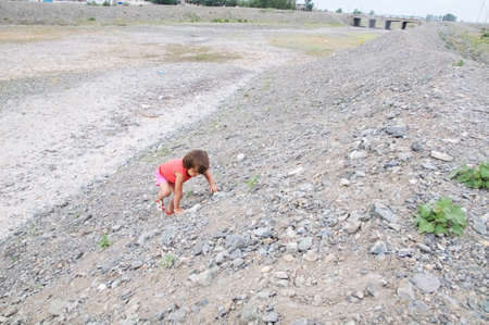 Child climbing the hill in dried river bed in Middle Asia Kazakhstan